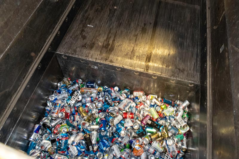 Cans are compacted in a large machine.